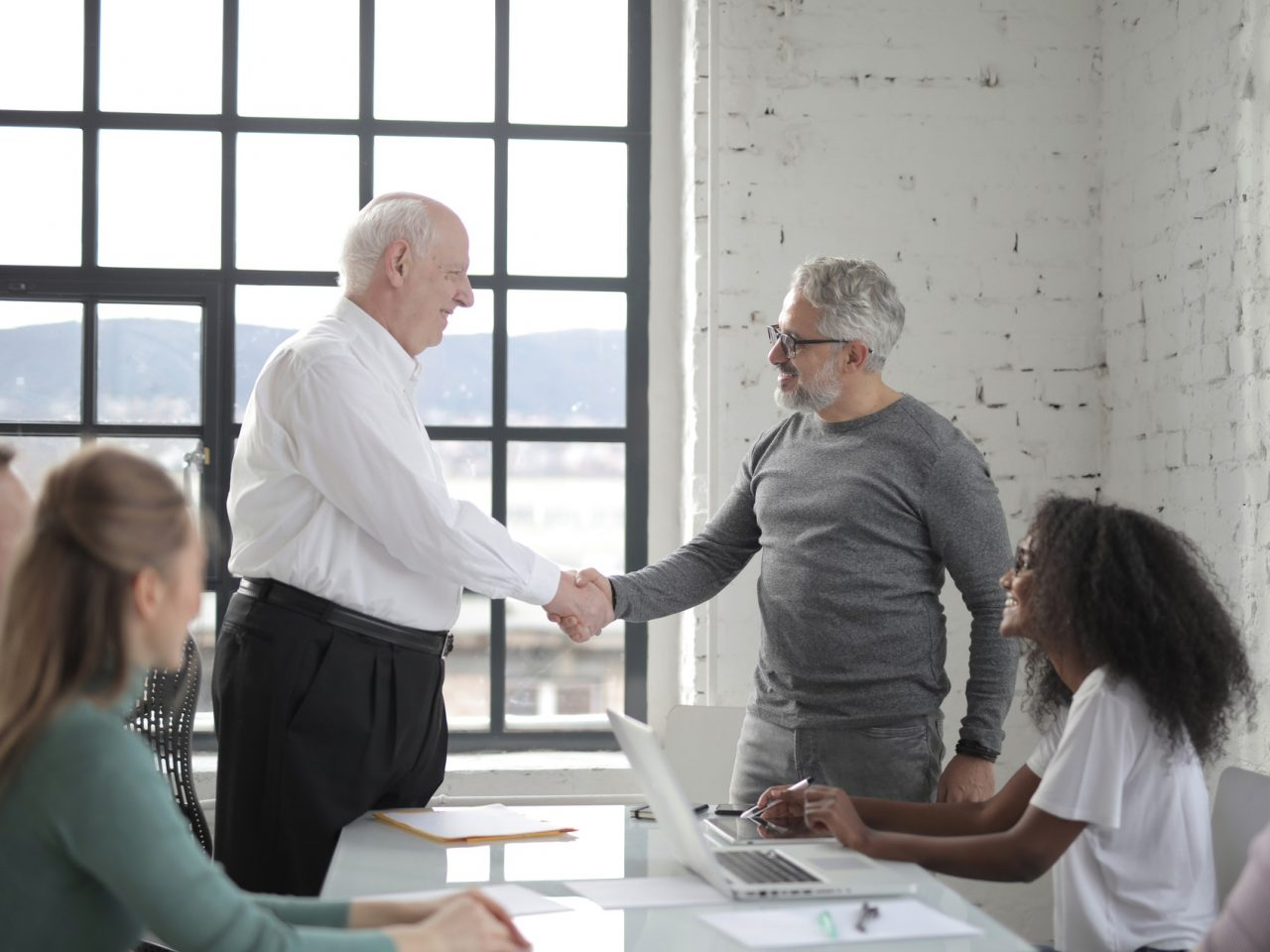 colleagues shaking hands in office